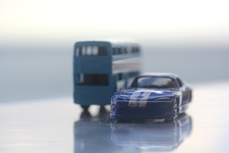 Miniature colorful blue bus standing next to dark blue car with reflection on a table with blue