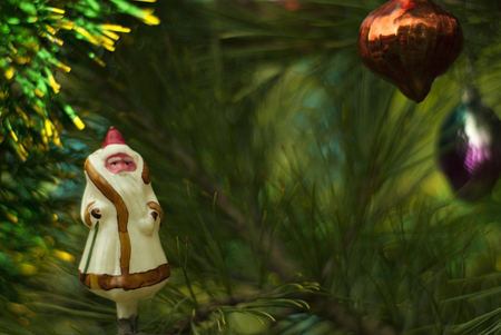 Vintage glass Christmas tree toy: Ded Moroz (Grandfather Frost,slavic analog of Santa Claus) in the background of green branches. Blurred background. Stock Photo