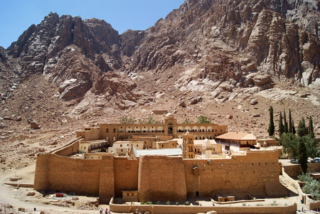 Monastery of St. Catherine Sinai (one of the oldest working Christian monasteries in the world) located a stony valley between the rocks. Noon. General view from above shot from the mountainside. Stock Photo