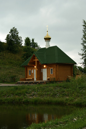a small modern building of the Orthodox baptistery, made in the traditional style of wooden architecture, standing near the lake