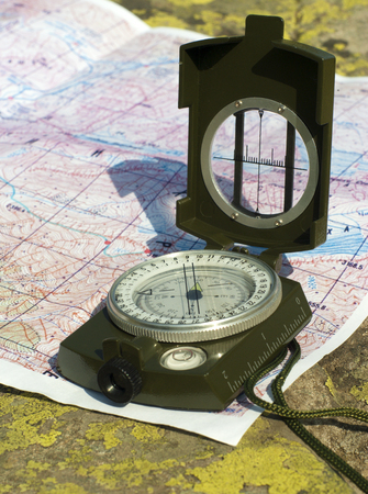 a compass and a mountain map lying on a lichen-covered natural boulder
