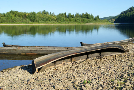 village fishing boats, dragged to the pebbled shore of the Ural river Vishera, on a clear summer day