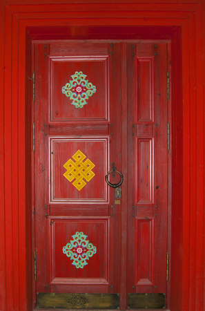 scarlet wooden door in Buryat or Tibetan style (in Buddhist datsan - monastery) with a bronze handle-ring and national patterns, in full frame