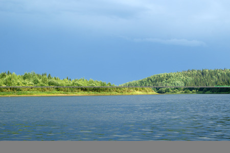 sunlit shore of the Ural river Vishera with a thundercloud in the background; view from the water