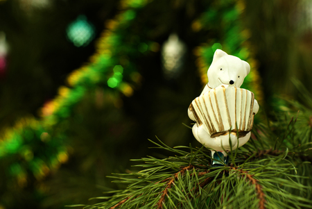 retro, glass, hand painted Christmas ornament - white bear-accordionist- on a background of a blurred Christmas tree