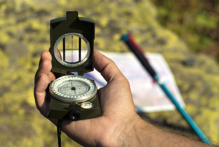 Professional geological compass in the man`s hand closeup. On a blurry background can distinguish a map spread out on a stone and leaning poles for a nordic walking. Stock Photo