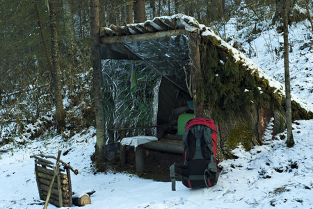Improvised, deliberately primitive lean-to shelter from poles, bark and branches in the winter snow-covered forest. In the foreground is a red modern backpack.