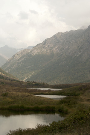 A view of the mountain ranges of the Caucasus, covered with clouds, from a mountain pass. In the foreground there are three small mountain lakes almost round in shape, one after another.