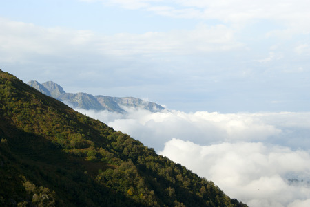 a view from above on cumulus clouds to the horizon, from which mountain ridges rise