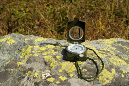 a professional geological compass lies on a lichen covered natural boulder outdoor