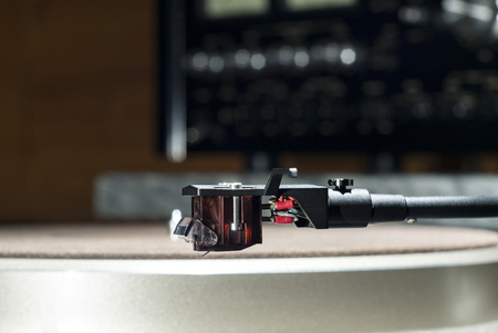 Moving magnet cartridge on the tonearm on a blurred background Stock Photo