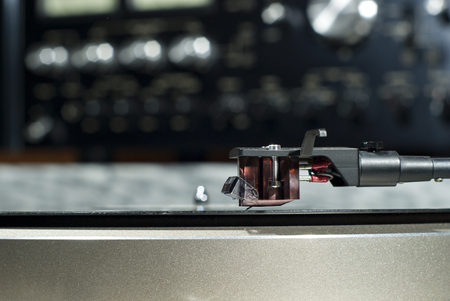 Moving magnet cartridge on the tonearm standing on a vinyl record