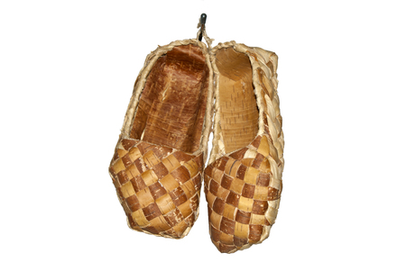 traditional ancient woven bast shoes hanging on the wall isolated