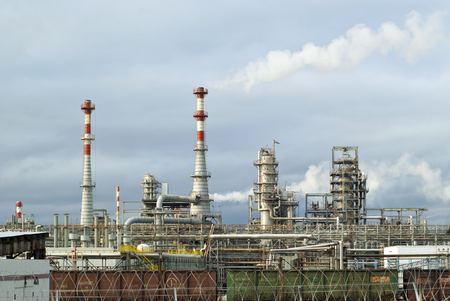 general view of a chemical or oil refinery with a multitude of pipelines, factory pipes, distillation columns and freight cars in the foreground under a cloudy sky Editorial