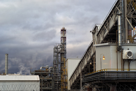 a fragment of some large refinery with a variety of technical designs, a distillation column, a covered conveyor structure and burning lanterns in the evening Stock Photo