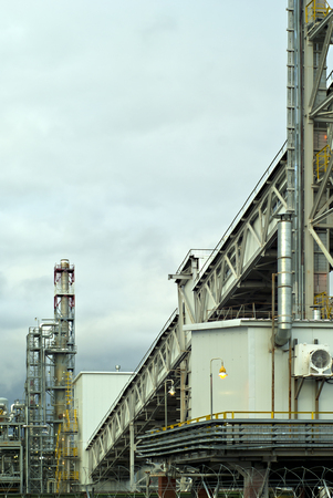 a fragment of some large refinery with a variety of technical designs, a  fractionating column, a covered conveyor structure and burning lanterns  Stock Photo