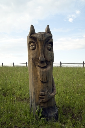 RUSSIA, PARMAYLOVO - JULY 15, 2017: rough wooden sculpture of an imp, made of stump, standing in a field in the open air