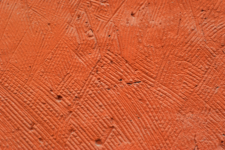 background, texture: orange, deliberately coarse plastered wall of a building close-up