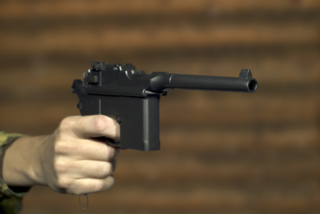 A mans hand with a vintage semi-automatic pistol points past the frame on the background of a log wall.