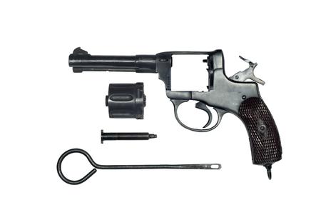 ontmanteld vintage revolver met de cilinder verwijderd en de laadstok in de vorm van afzonderlijke delen op een witte achtergrond