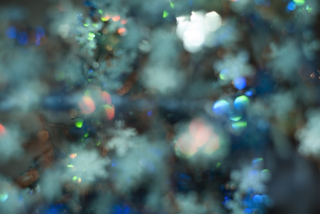abstract blue festive blurred background in which the outlines of snowflakes or a decorated Christmas tree are guessed