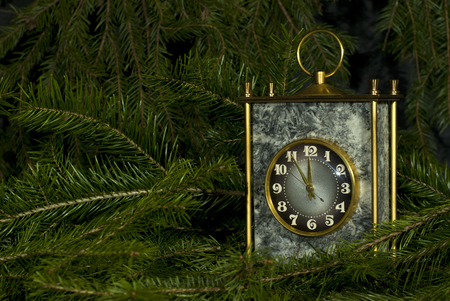 Vintage desk clock in a gray stone block with brass details among the fir branches 写真素材