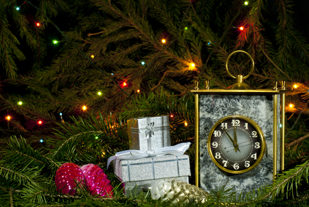 Vintage desk clock, several small packaged gifts and Christmas ornaments among fir branches on a dark background with lights of a glowing garland