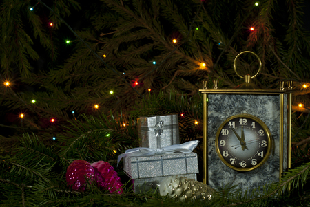 Vintage desk clock, several small packaged gifts and Christmas ornaments among fir branches on a dark background with lights of a glowing garland Stock fotó