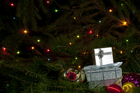 A pair of small Christmas gifts and a few Christmas ornaments among fir branches on a dark background with colorful lights of a garland