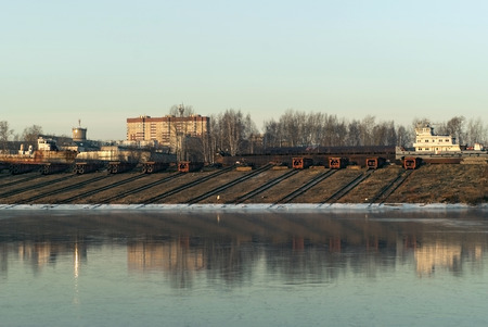 slipways with roller-pallets of ship repair yard for river vessels on the shore of the winter canal