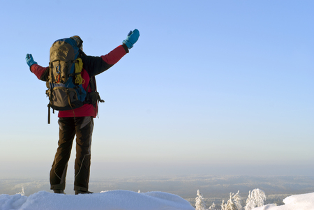 traveler man with a backpack on top of the winter mountain spread his arms, admiring the scenery