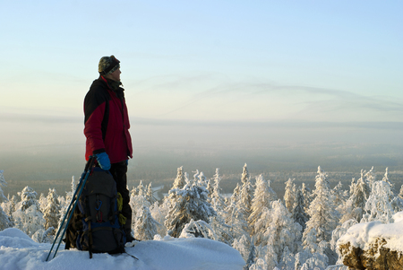 Traveler man with a backpack on top of the winter mountain looks back at the path, admiring the scenery