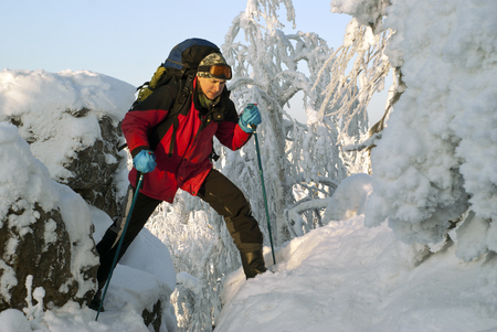 traveler man with a backpack in a beautiful winter mountain landscape oversteps the precipice