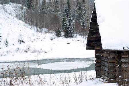 fragment of an old log hunting cabin on the river bank in a winter landscape