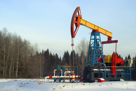 A bright pump jack over an oil well in a winter snowy forest landscape