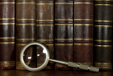 background : A row of worn leather antiquarian book spines with gold embossing and a magnifying glass Stock Photo
