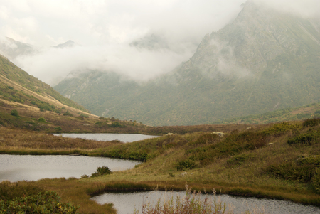 three strange round small karst lakes on a scenic mountain pass with a cloud covered mountain ridge in the background