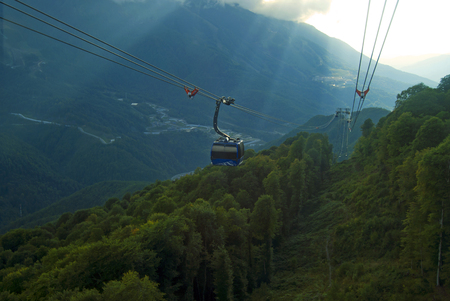 view from the window of the cable car to the mountain valley in cloudy weather with sun rays breaking through the clouds   Stock Photo