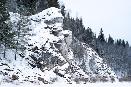 A picturesque rock on the shore of a winter frozen pond in the wooded mountains 写真素材