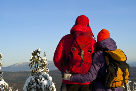 a man and a woman in warm sports clothes with backpacks, stand their back to the viewer, embracing and looking at the winter mountain landscape Stock Photo