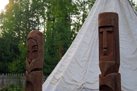 two heathen wooden totems in front of a traditional tent (chum or tipi) closeup against a forest close-up background