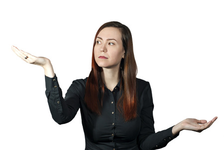 the girl on a white background holds her palms like a bowls of scales and looks thoughtfully at one hand, as if weighing the pros and cons