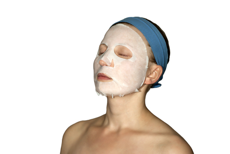 young woman with closed eyes with paper cosmetic mask on face