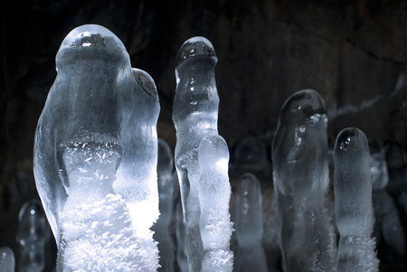 group of transparent ice stalagmites in a cave closeup on a dark background