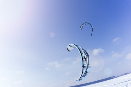 PERM, RUSSIA - FEBRUARY 23, 2018: two kites for snowkiting, rushing low over the snow against the sky 에디토리얼