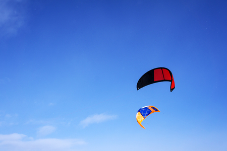 two multicolored sports kites for kiting or snowkiting on a background of blue sky with clouds