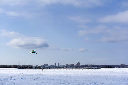 PERM, RUSSIA - MARCH 09, 2018: snowkiter rides on the ice of the Kama Reservoir on city background