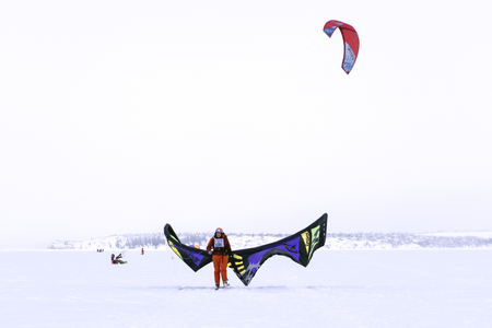 PERM, RUSSIA - MARCH 09, 2018: snowkiters are preparing to start during a snowfall on the ice of a frozen pond