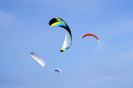 four bright multicolored sports kites for kiting or snowkiting against the blue sky