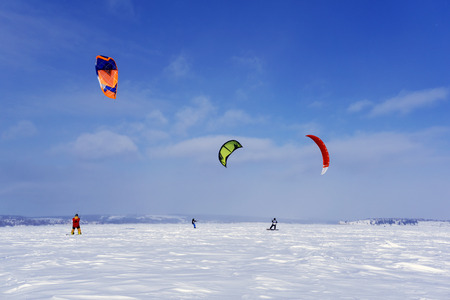 PERM, RUSSIA - MARCH 09, 2018: snow kiters train on the ice of a frozen lake in the background of a winter landscape 에디토리얼
